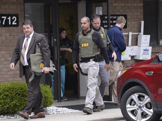 FBI agents leave the office of Dr. Fakhruddin Attar at the Burhani Clinic in Livonia on Friday morning after completing a search for documents.