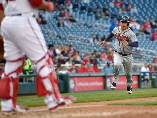 Atlanta Braves' Daniel Castro runs towards home to score on a double by Nick Markakis during the eighth inning of a baseball game as Washington Nationals catcher Wilson Ramos waits at left Thursday, April 14, 2016, in Washington. The Nationals won 6-2. (AP Photo/Nick Wass)