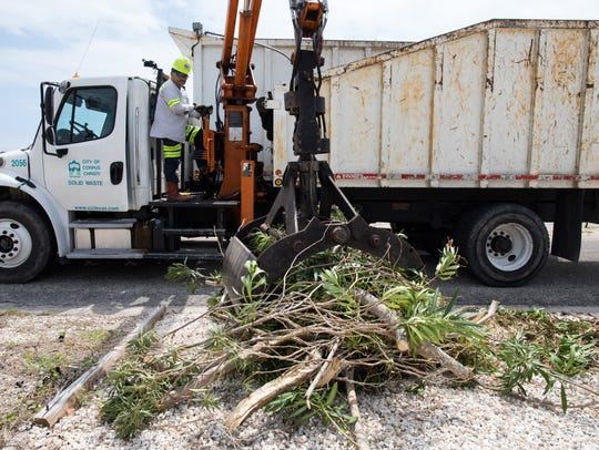 A Corpus Christi solid-waste worker picks up debris