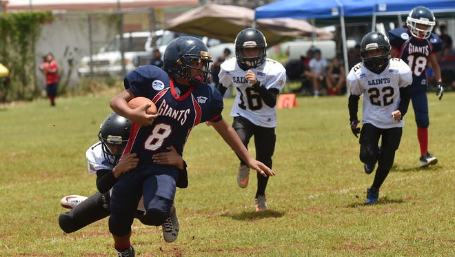 Giants player Eugene Arriola is tackled by a Saints defender during their Triple J Ford GNYFF Youth Football game at Raiders Tiyan Field on Aug. 23.