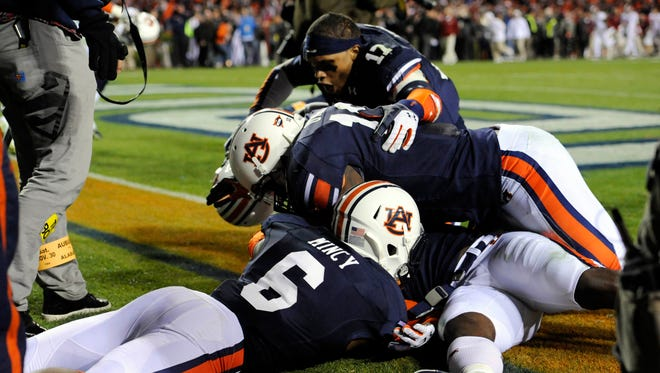 Auburn Tigers cornerback Chris Davis (bottom) celebrates with defensive back Jonathon Mincy (6) and teammates after returning a missed field goal for a 100 yard touchdown during the fourth quarter at Jordan Hare Stadium. Auburn Tigers won 34-28.