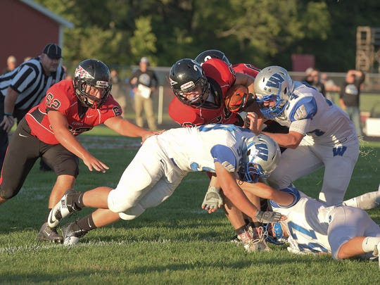 Despite being on the ground already, Cole Heinlen still does whatever he can to wrap up Bucyrus' Zane Seybert earlier in the season.