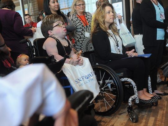 Kendra Gottsleben, Vicki Harkness and others listen during a news conference to publicly commemorate the 25th anniversary of the signing of the Americans with Disabilities Act at the Hilton Garden Inn Downtown Sioux Falls on Monday, July 13, 2015.