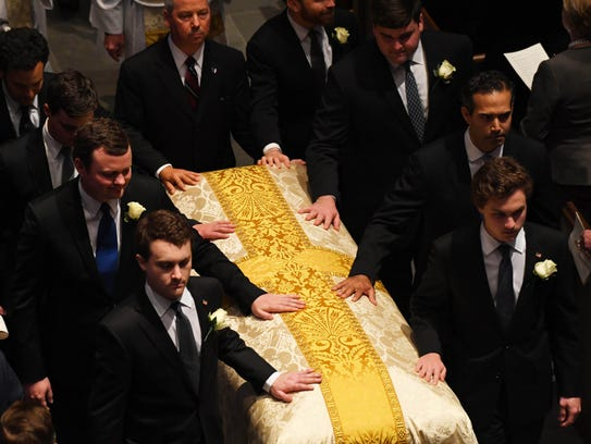 Bush grandsons as pallbearers, exit following the funeral