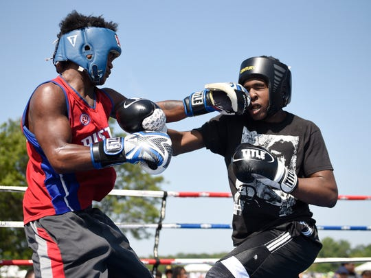 Deonte Cheeves, 18, left, and DeAndre Madison, 15, battle in the ring during a match that was part of Metro Detroit Youth Day on Wednesday.