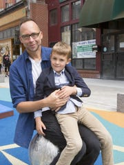 Six-year-old Hudson Westphal of Ithaca, and dad Andrew were the first people to officially use the new playground on The Commons after it opened Wednesday.