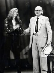 Emmylou Harris and Bill Monroe appear on stage during