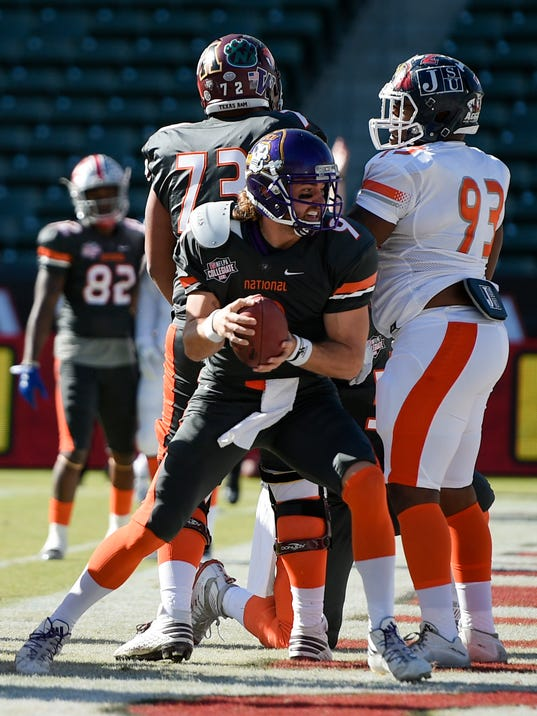 National Team quarterback Philip Nelson (9), of East Carolina, runs in a touchdown as American Team defensive tackle Cornelius Henderson (93), of Jackson State, looks on during the first half of the NFLPA Collegiate Bowl football game in Carson, Calif., Saturday, Jan. 21, 2017. (AP Photo/Kelvin Kuo)