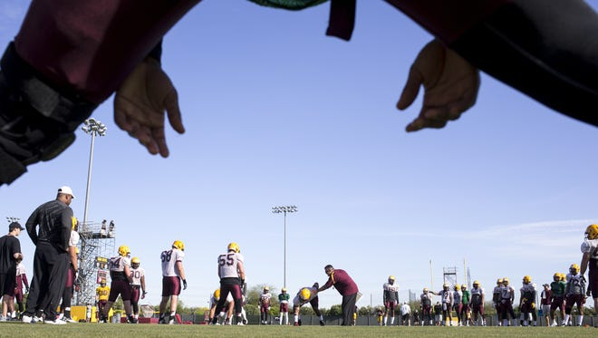 ASU's Todd Graham (center) works with a player on March 24, 2015 during spring football practice.
