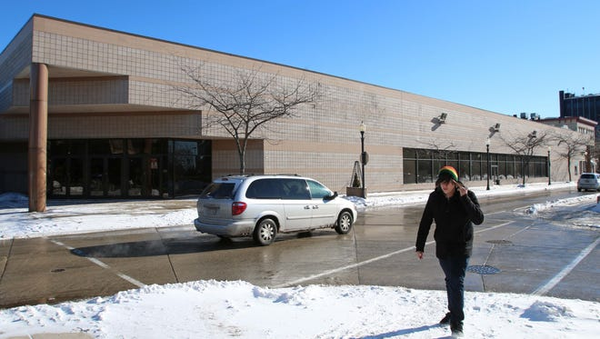 A pedestrian walks by the sign-less exterior of Boston Store Thursday January 23, 2014 which is slated to be closed by the end of the month.
