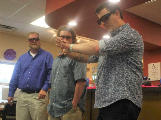 Ian Wilson (right) checks out his tattoos for the first time in color Friday morning as Mark Yeager (left) and Tim Masters look on.