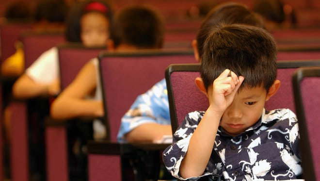 First-grader Mathew Sie, 6, from Chino Hills, Calif., keeps a sharp eye on his test questionaire during the annual Kumon Math Challenge at the University of Southern California, Sunday, July 11, 2004, in Los Angeles, Calif. (AP Photo/Kumon Math Centers, Bob Riha, Jr.)
