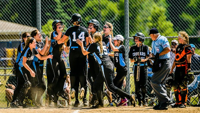 Megan Doyle ,14, of Lansing Catholic greets her teammates at homeplate after hitting her second homerun of the game in the 4th inning.  The 3 run blast cut the Alma lead to 1.