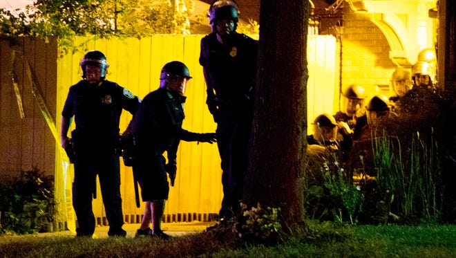 Police take cover behind a tree and home after shots were fired at the scene of unrest Aug. 13 after officers fatally shot a man in the Sherman Park neighborhood.