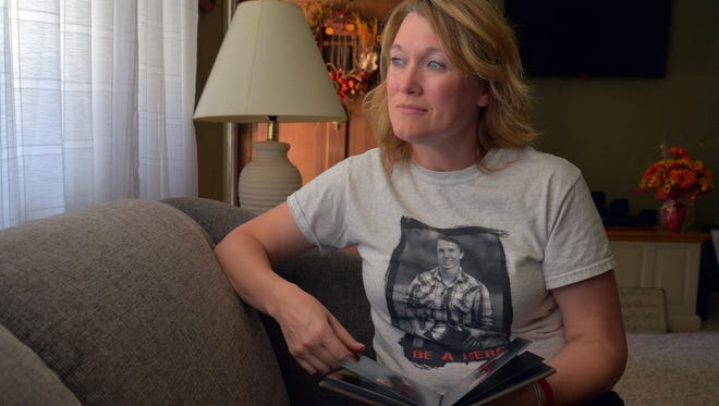Sandy Cates holds a photo album of her son Justin