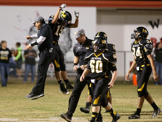 Menard's Brody Baugh jumps up to celebrate with a coach during the Yellowjackets' 52-20 win over Miles on Nov. 17, 2017, in a Class 2A Division II bidistrict playoff game at Bearcat Stadium in Ballinger.