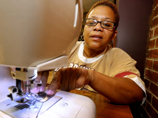 Charlene Triche works on a sewing machine donated by