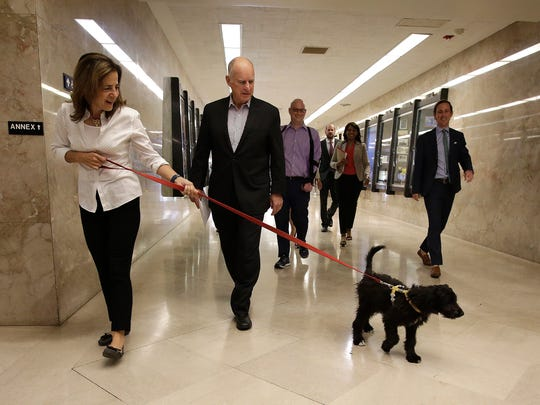 As he walks through the Capitol on Friday to deliver his revised 2018-2019 state budget plan, Gov. Jerry Brown, center, is accompanied by his wife, Anne Gust Brown and Cali, the newest member of the Brown family.