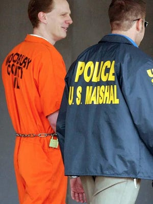 Dustin Lee Honken is led by U.S. Marsahl Oct. 27, 2004 from the federal building in Sioux City.