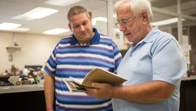 Don Lindley, who just visited all 92 counties in Indiana, shows his log book to Delaware County Clerk Mike King who would stamp the final county in his book. Lindley traveled 3425 miles around the state to reach all the county courthouses.