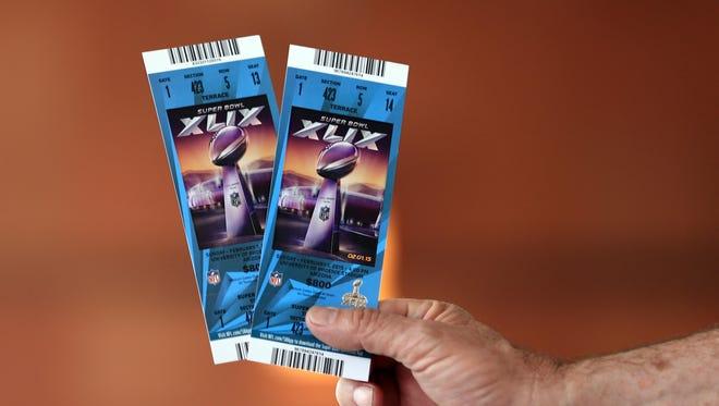 Feb 1, 2015; Glendale, AZ, USA; A fans holds Super Bowl XLIX tickets at the StubHub ticket center in the Glendale Renaissance.