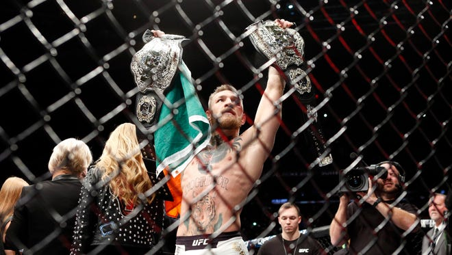 Conor McGregor  celebrates with his two championship belts after defeating Eddie Alvarez at Madison Square Garden.