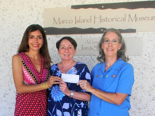 Pat Rutledge, center, accepts a donation for the Marco