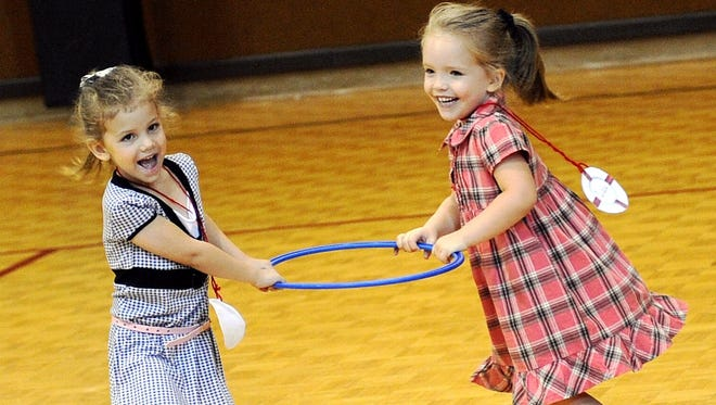 Two young girls play during some free time at the gym during First Christian Church's vacation Bible school in this file photograph. Churches are readying for this summer's slate of vacation Bible school.