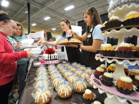 Riley Gelb, 11, and Leslie McDermott, from left, sample bite-sized cakes from Kelsey Lankford and Jamie Mehula in Nothing Bundt Cakes' booth during the 2016 Chocolatefest at Knoxville Expo Center.