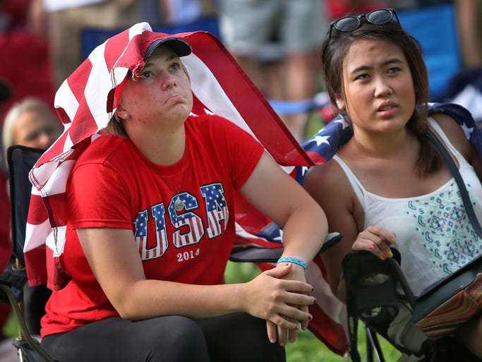 Emma Hass, left, and Prae Kampee look on as the United States is defeated by Blegium in the World Cup, watching the game at the World Cup block party in Carmel, Tuesday, July 1, 2014.