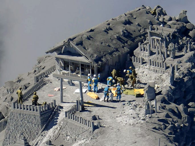 Rescue workers search buildings for missing people after Mt. Ontake sudenly erupted on Sept. 29 in Nagano, Japan. Thirty-one people died in the Sept. 28 eruption.