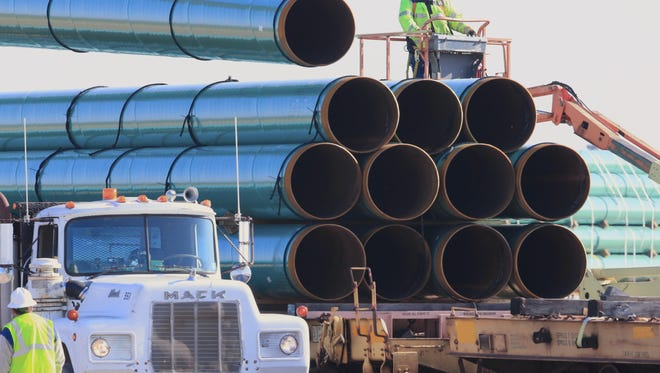 Workers unload pipes for the proposed Dakota Access oil pipeline, which would stretch from the Bakken oil fields in North Dakota to Patoka, Ill.