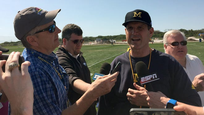 U-M coach Jim Harbaugh speaks to reporters.