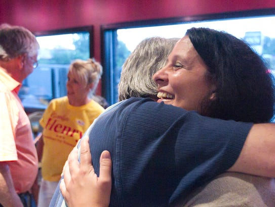 Jim Buttrey gives a hug to Carolyn Henry, candidate
