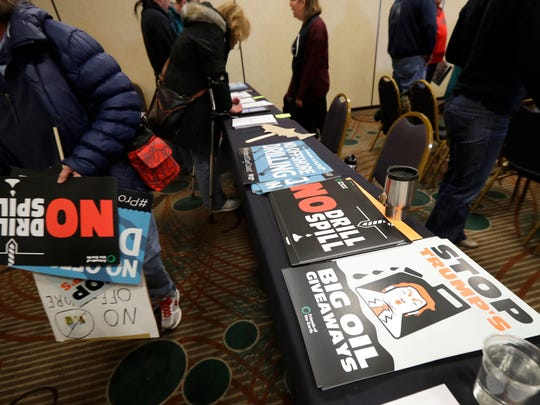 Signs opposing offshore oil drilling are distributed, Monday, March 5, 2018, at a hearing in Olympia, Wash., organized by a coalition of environmental groups opposed to the Trump administration's proposal to expand offshore oil drilling off the Pacific Northwest coast.