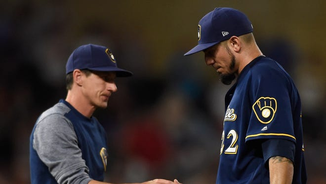 Manager Craig Counsell takes the ball from Matt Garza after the Brewers' starting pitcher allowed eight runs on eight hits, including four homers, in just 3 1/3 innings against the Twins on Tuesday night in Minneapolis.