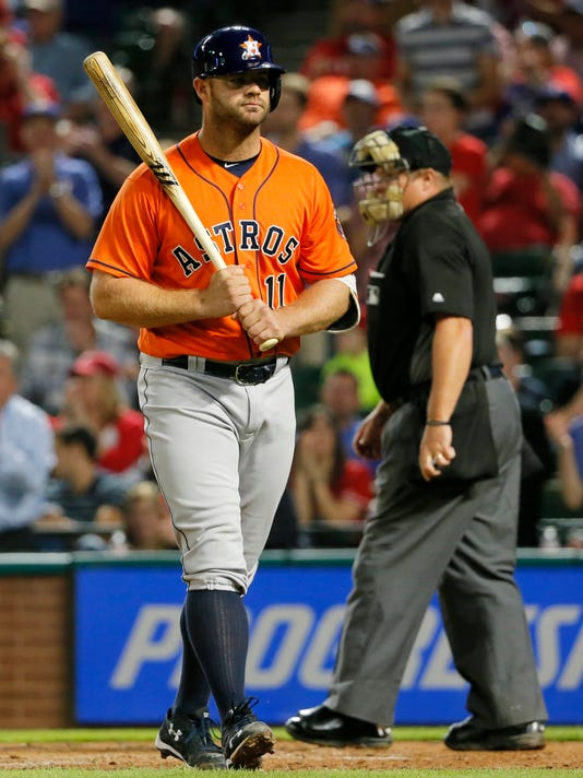 Houston Astros' Evan Gattis walks back to the dugout after striking out to Texas Rangers starting pitcher Jake Diekman during the eighth inning of a baseball game as umpire Marin Hudson remains by the plate, Wednesday, April 20, 2016, in Arlington, Texas. The Rangers won 2-1. (AP Photo/Tony Gutierrez)