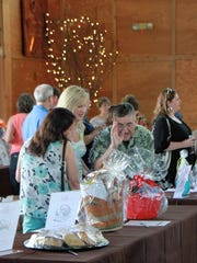 Bidding begins on silent auction items at the Marion-Polk Food Share Farm to Table Dinner & Auction.