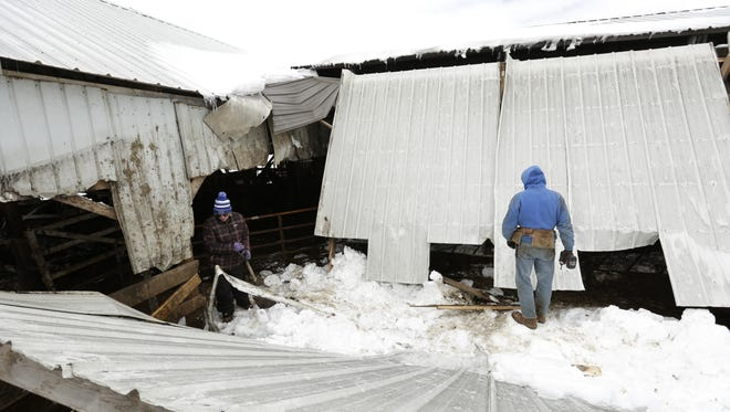 Jennifer and John Yost III take apart their barn roof Tuesday, April 17, 2018, in the 6500 block of Yost Road in the town of Winneconne. A buildup of ice and snow caused the roof to collapse onto three of their cows about 8:30 p.m. Monday, Winneconne-Poygan Fire Chief Ryan Krings said. Fire crews rescued the three cows.