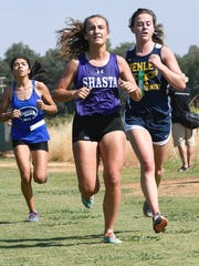 Shasta High runner Mia Fleming, center, works to stay