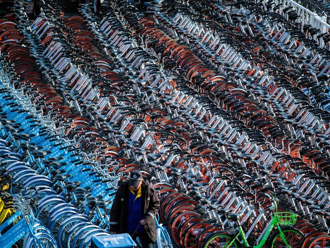 A man walks past impounded bicycles from the bike-sharing