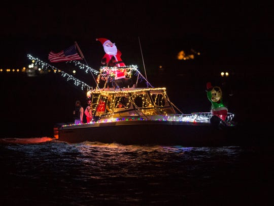 A boat decorated with lights and a Santa Claus passes Sandsprit Park on Dec. 3 2016 during the Martin County Christmas Boat Parade in Stuart.