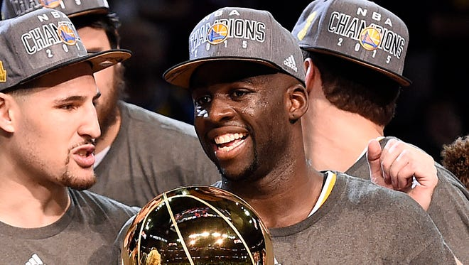 Golden State Warriors forward Draymond Green celebrates with the Larry O'Brien Trophy after beating the Cleveland Cavaliers in Game 6 of the NBA Finals at Quicken Loans Arena.
