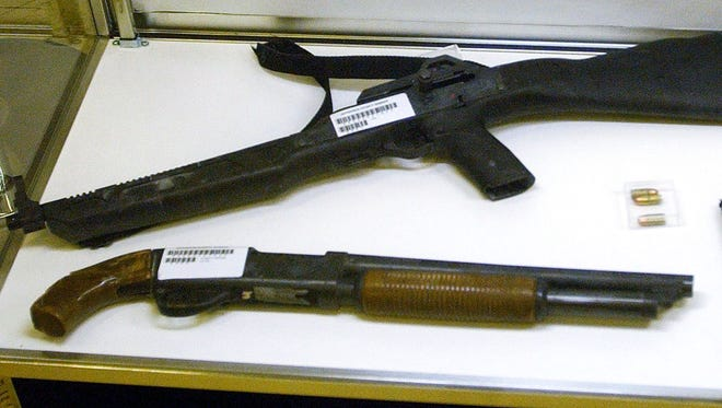 The 9mm carbine (top) and one of the sawed-off shotguns used by the Columbine High School killers are displayed Feb. 26, 2004. at the Jefferson County Fairgrounds in Lakewood, Colo.