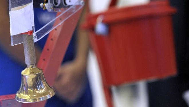 """The bell, attached to """"Sphyrna 19.5"""" rings in front of the Salvation Army Red Kettle."""