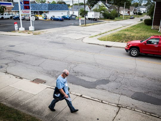 Cracks and potholes mar the pavement near the intersection of Jackson and Calvert Streets Tuesday afternoon.