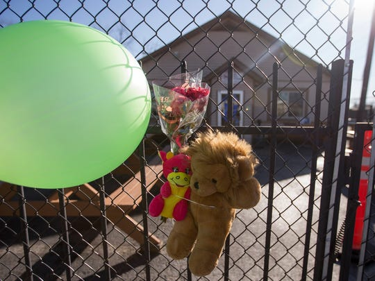 Offerings attached to a fence outside the Sawmill Saloon, on the 1300 block of North Sherman Drive, the scene of an early morning quintuple shooting Indianapolis, Sunday, Jan. 28, 2018. Two people died, and three more were injured.