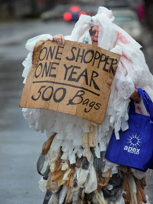 Susanne Galligan, dressed in plastic bags to represent personal waste, yells to cars passing by during an Earth Day 2015 celebration in Glens Falls, Warren County.