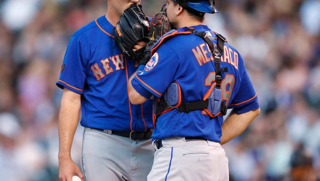 New York Mets starting pitcher Seth Lugo, left, confers with catcher Devin Mesoraco while facing Colorado Rockies' Trevor Story during the third inning of a baseball game Wednesday, June 20, 2018, in Denver.