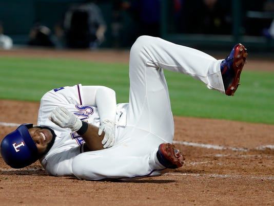 Texas Rangers' Elvis Andrus rolls on the ground by home plate holding his right elbow after being hit by a pitch from Los Angeles Angels' Keynan Middleton in the ninth inning of a baseball game in Arlington, Texas, Wednesday April 11, 2018. Andrus left the game with an unknown injury. (AP Photo/Tony Gutierrez)
